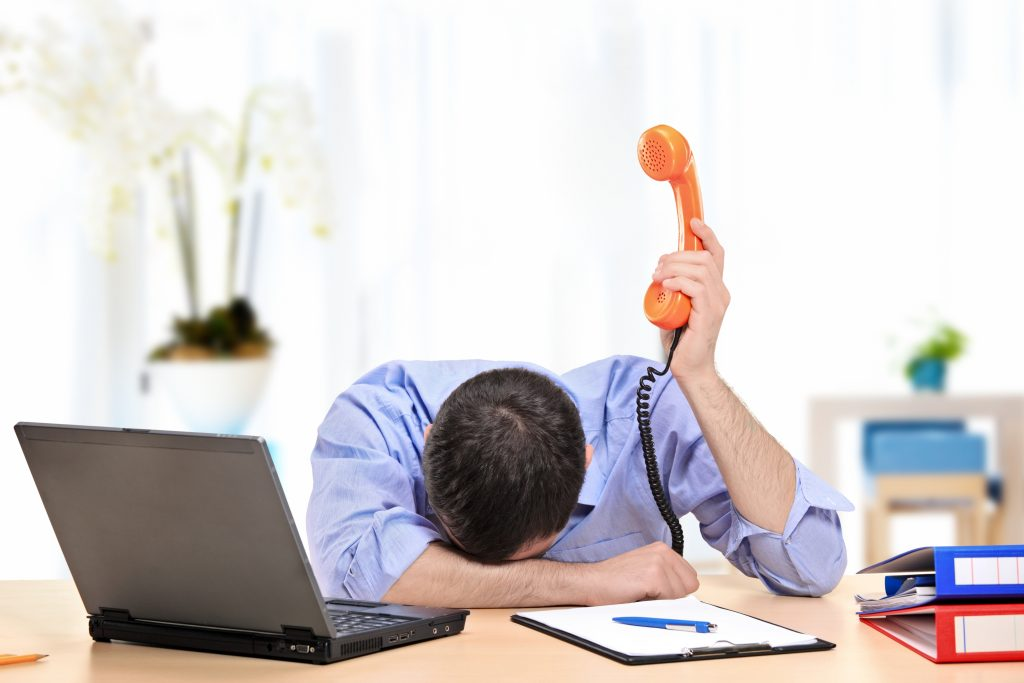 An exhausted businessman holding a telephone while conducting a telephone interview from his office
